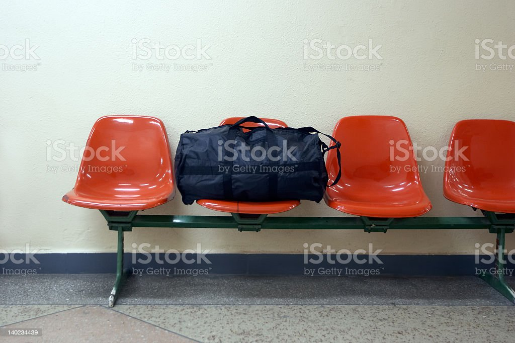 Single black duffel bag on a row of red chairs royalty-free stock photo