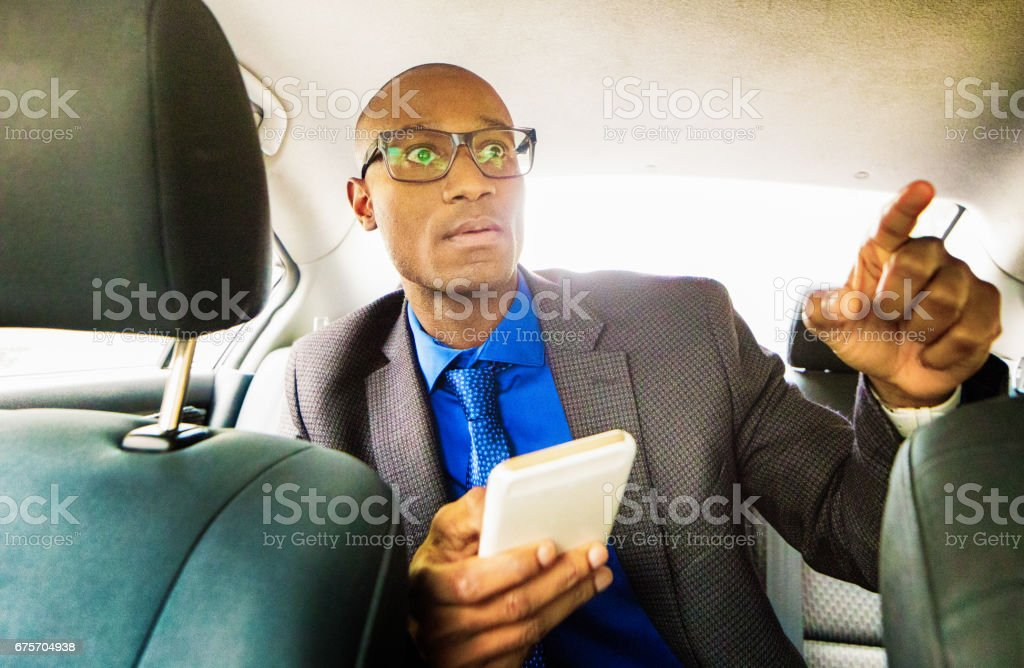 Single black male back seat driver with mobile phone royalty-free stock photo