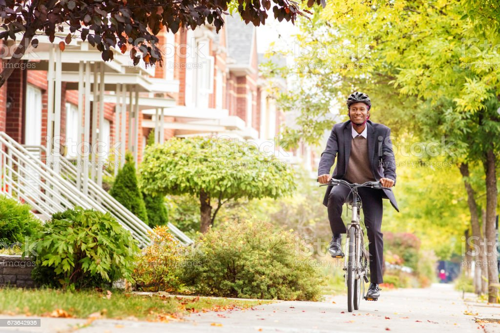 Single black male in his 30s cycling on urban sidewalk in Autumn stock photo
