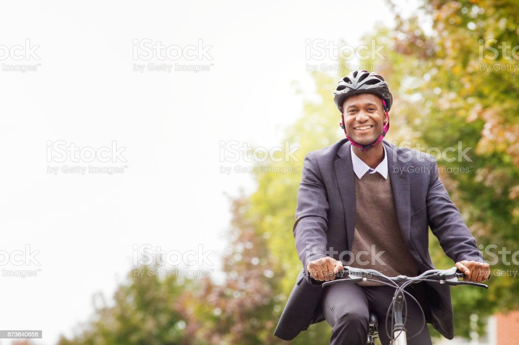 Single black male in his 30s smiling as he cycles to work stock photo