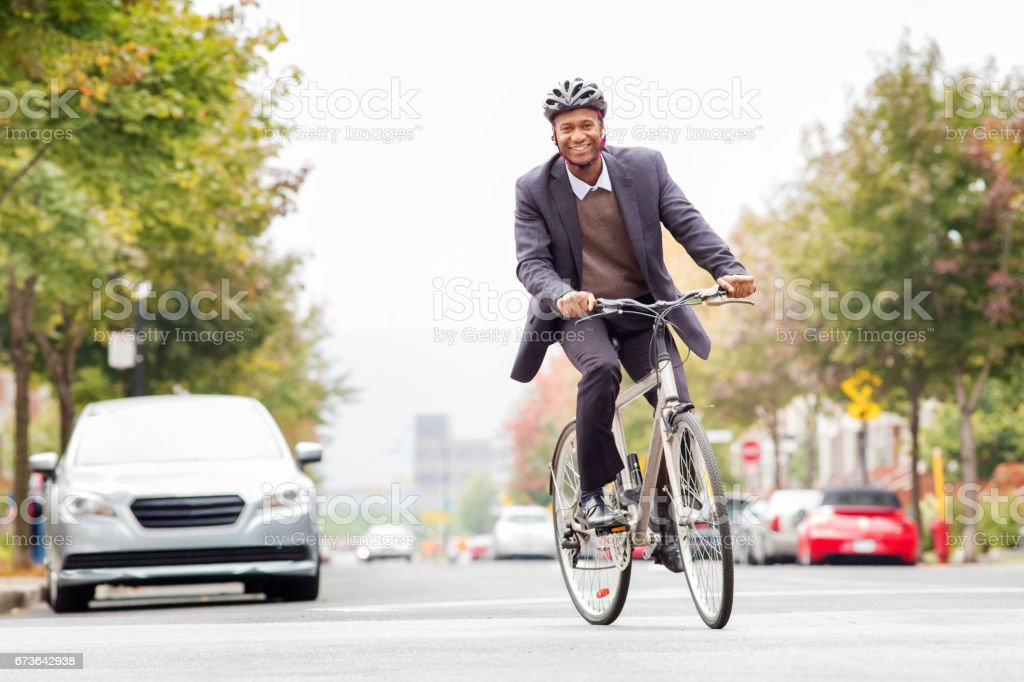 Single black male in his 30s smiling while commuting to work by bicycle stock photo