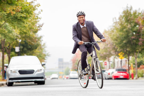 single black male in his 30s smiling while commuting to work by bicycle - cycling stock photos and pictures