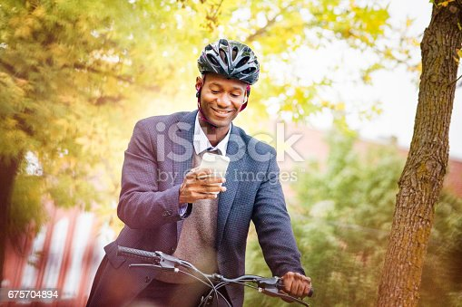 istock Single black male in his 30s text messaging while riding his bicycle 675704894