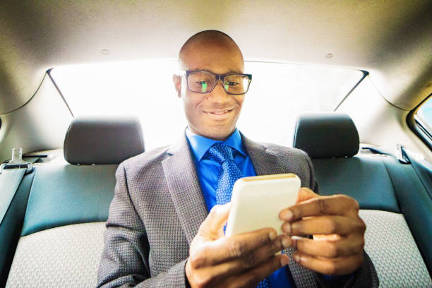 Single black male mid adult text messaging on mobile phone car back seat stock photo