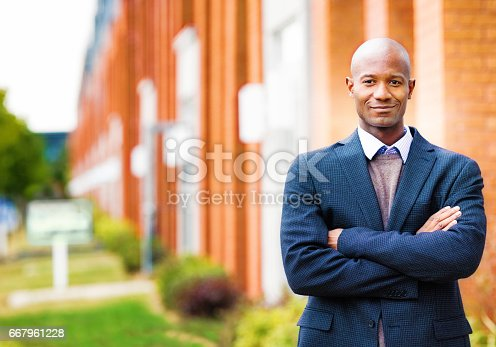 Single black man in suit smiling Autumn portrait arms crossed with real estate background