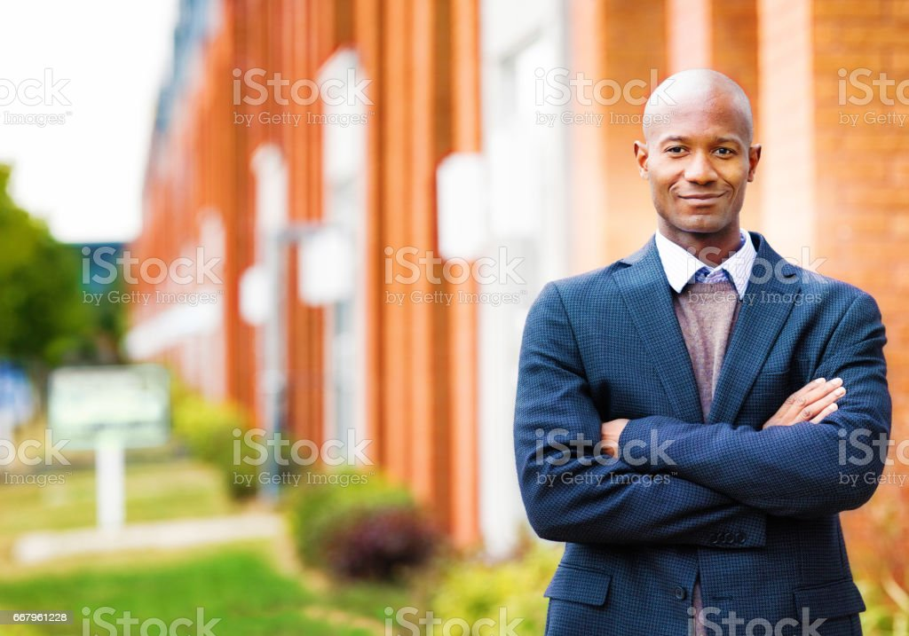 Single black man in suit smiling portrait with real estate background stock photo