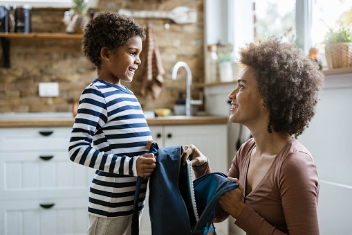 Happy African American mother talking to her small son while packing his books into a backpack.
