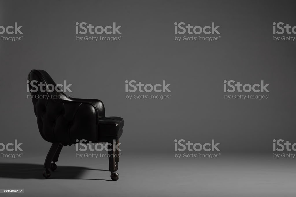 single black vintage leather chair in front of a grey background