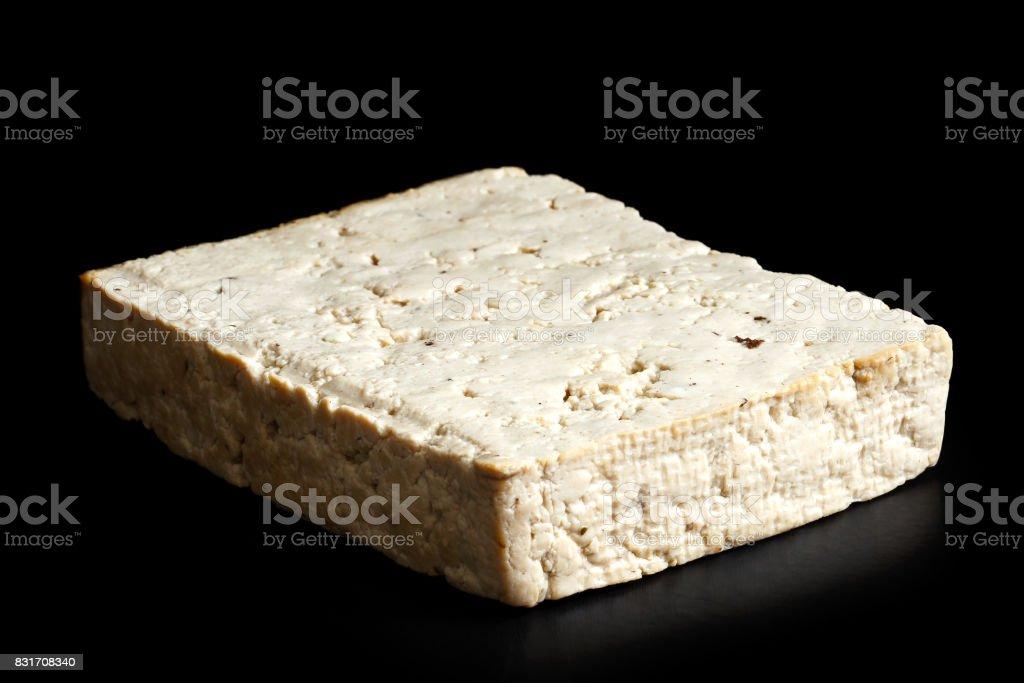Single block of lightly smoked tofu isolated on black. stock photo