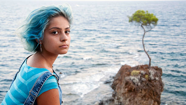 single blue-haired young girl and  a pine tree stock photo