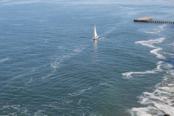 A Single Boat on the Ocean A sailboat leaving the dock jude beck stock pictures, royalty-free photos & images