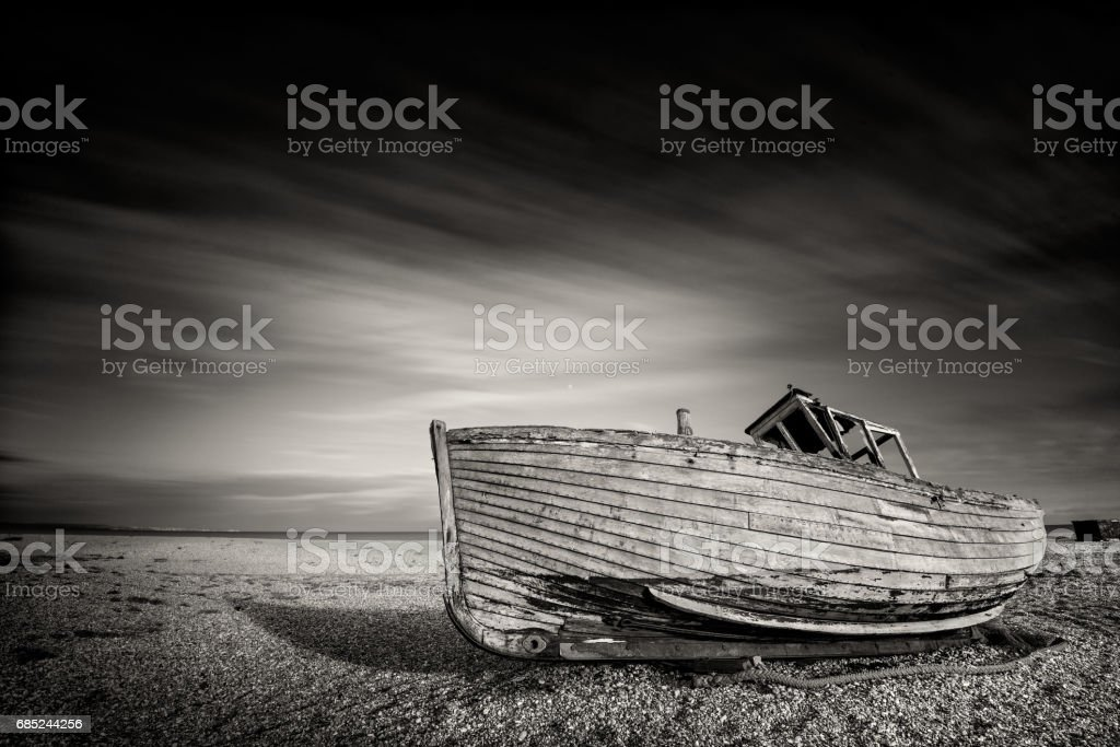 Single boat stranded on pebbled beach. Dungeness, England royalty-free stock photo