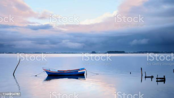 Photo of Single boat tied to a stake in the middle of the lagoon