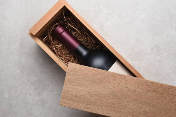 en enda flaska rött vin i en trä låda - wine box bildbanksfoton och bilder