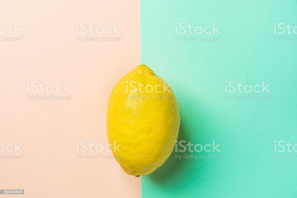 Single Bright Ripe Yellow Lemon on Contrast Background from Combination of Pink Peachy Turquoise Background. Styled Creative Image. Tropical Fruit Vacation Summer Beach Party Vegan Concept. Copy Space stock photo