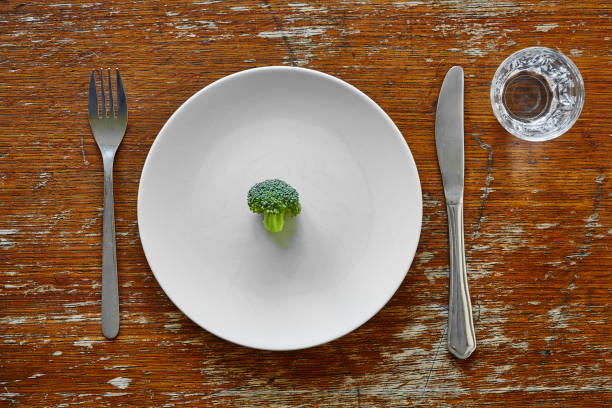 single broccoli on plate with knife and fork metaphor for dieting - szczupły zdjęcia i obrazy z banku zdjęć