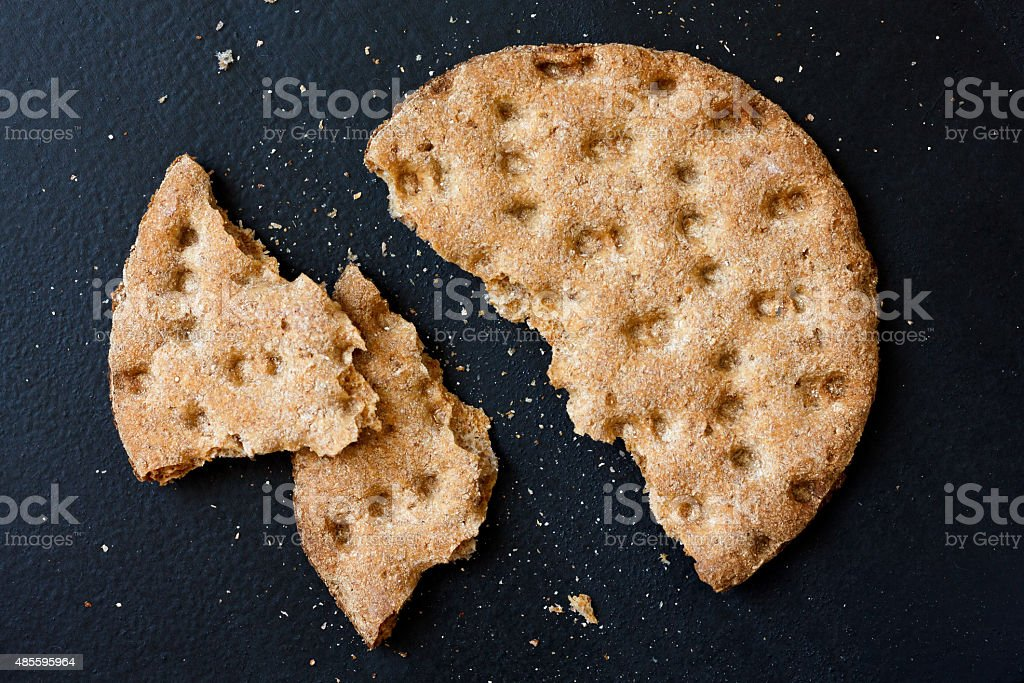 Single broken rye crispbread from above isolated on black. stock photo