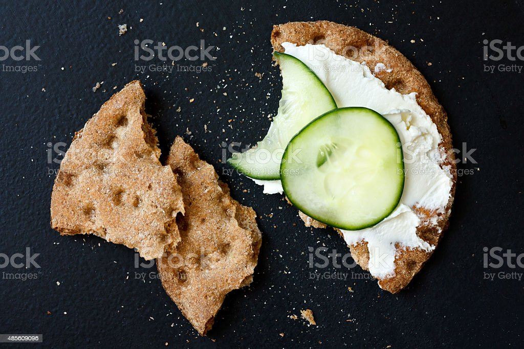 Single broken rye crispbread with cream cheese and cucumber, stock photo