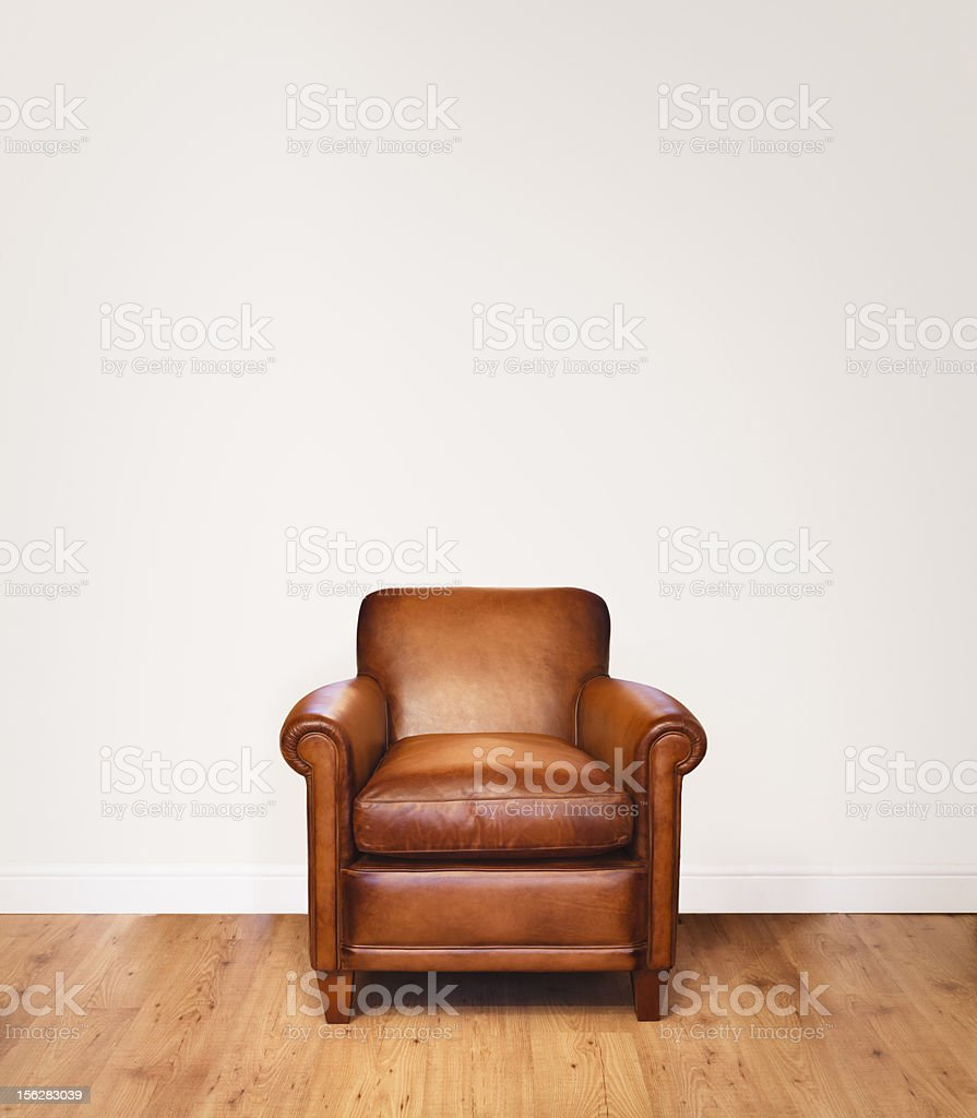 Single brown leather armchair on a wood floor stock photo