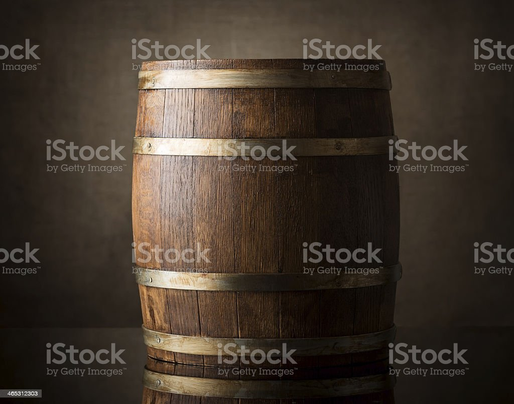 Single brown wine barrel with metal straps in dimly lit room stock photo