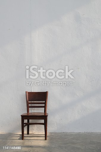 single wooden chair with light ray from window on white wall background.