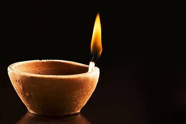 Single Burning Flame in an Earthen Lamp stock photo