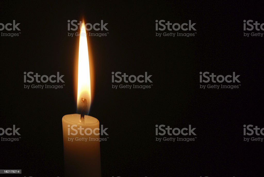 Single candle flame on horizontal black background stock photo
