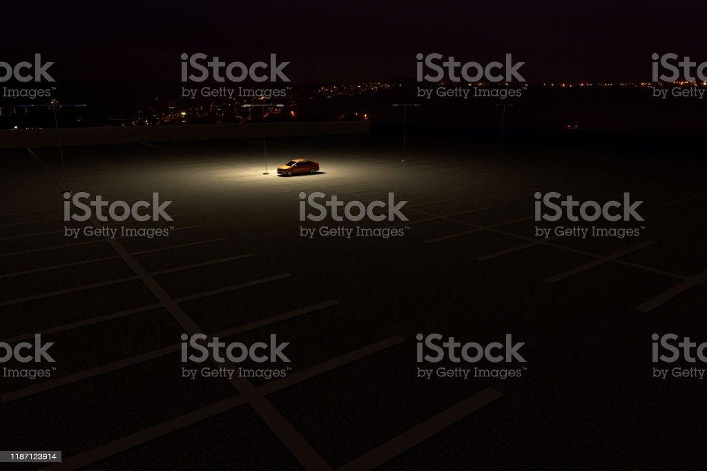 Un solo coche en un aparcamiento que representa el concepto de trabajar hasta tarde - Foto de stock de Abandonado libre de derechos