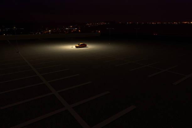 une seule voiture dans un parking représentant le concept de travailler tard - voiture nuit photos et images de collection