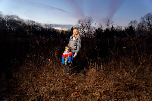 Einzelne kaukasische Mutter Wanderungen mit ihrem neugeborenen Kind an seiner Brust Geschirr an einem Moody Herbst Tag befestigt – Foto