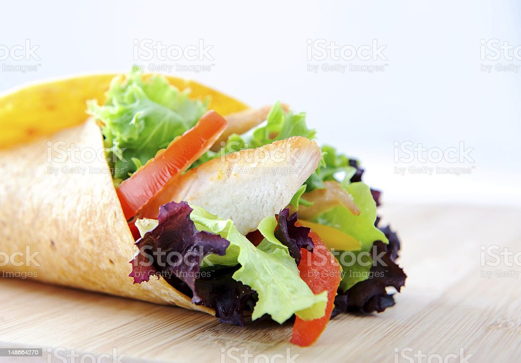 Single chicken burrito on wooden board with copyspace stock photo