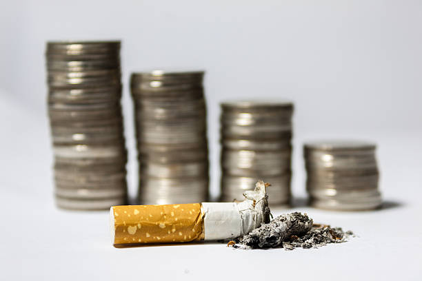 Single cigarette butt with ash and coin stack stock photo