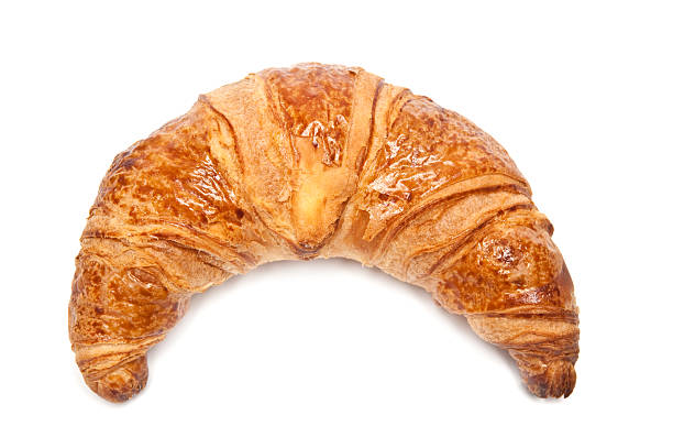 A single croissant against a white background stock photo