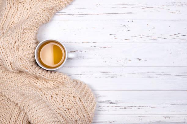 Einzige Tasse Tee und Beige Karomuster auf weißem Hintergrund aus Holz. – Foto