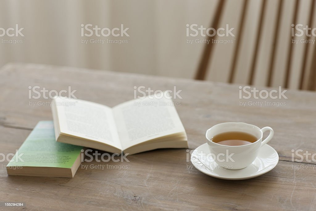 A single cup of tea on a wooden table with books stock photo
