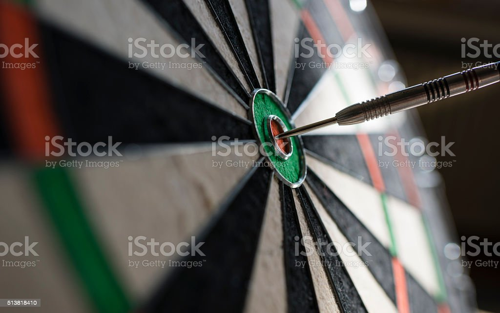Closeup view of one single dart sticking in the bull\'s eye of a...