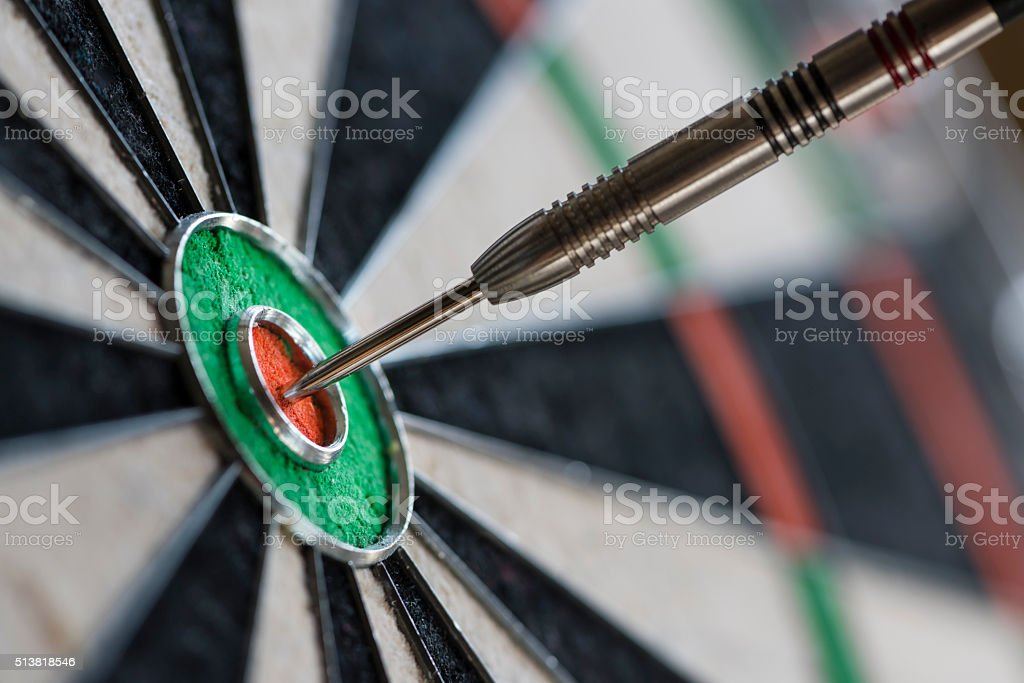 Single dart hitting bull's eye on the dartboard stock photo