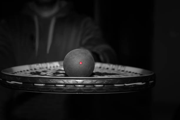 Single dot squash ball on the strings of a racquet stock photo