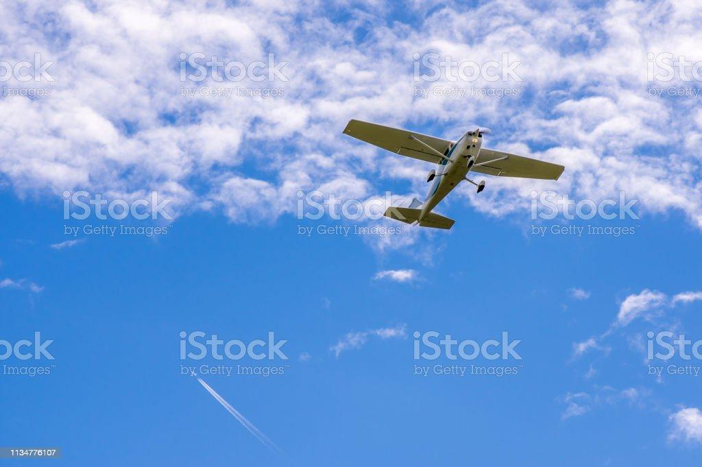 Einzelmotor-Sport-Flugzeug in der Luft vor Wolken, Kondensstreifen eines Jets im Hintergrund – Foto
