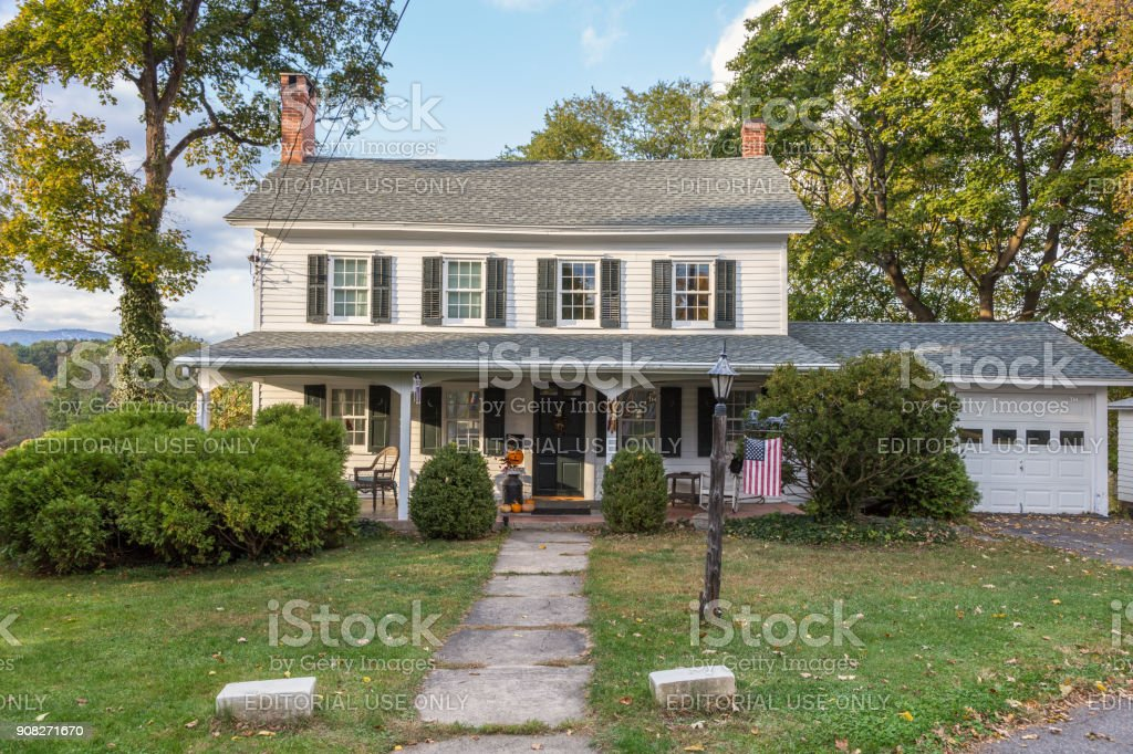 Single Family Home with White Clapboard Exterior and Trees in Autumn Colors (Foliage) in New Paltz, Hudson Valley, New York. stock photo