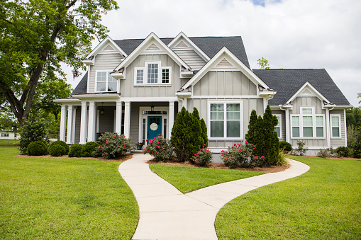 This is a single family home that is new construction cottage style house with hardy board and a partial metal roof. It is grey with a teal door and there is great curb appeal. The house has a double front entrance and it is on a large lot.