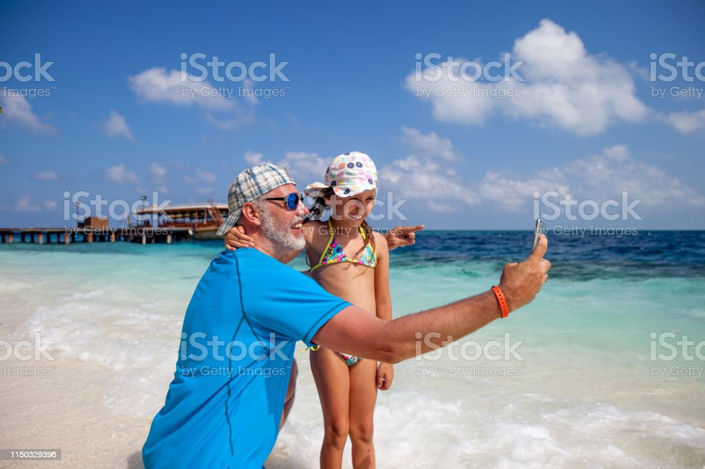 Single Father and Daughter on Tropical Island\'s Coastline.