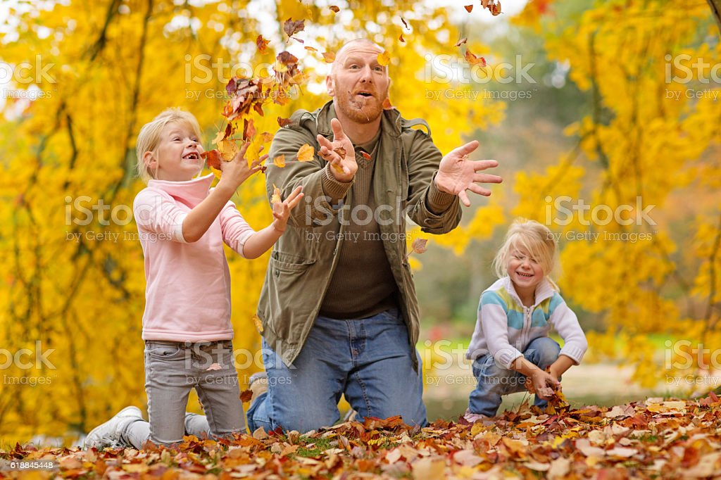 Single father and daughters playing together in autumnal park surroundings stock photo