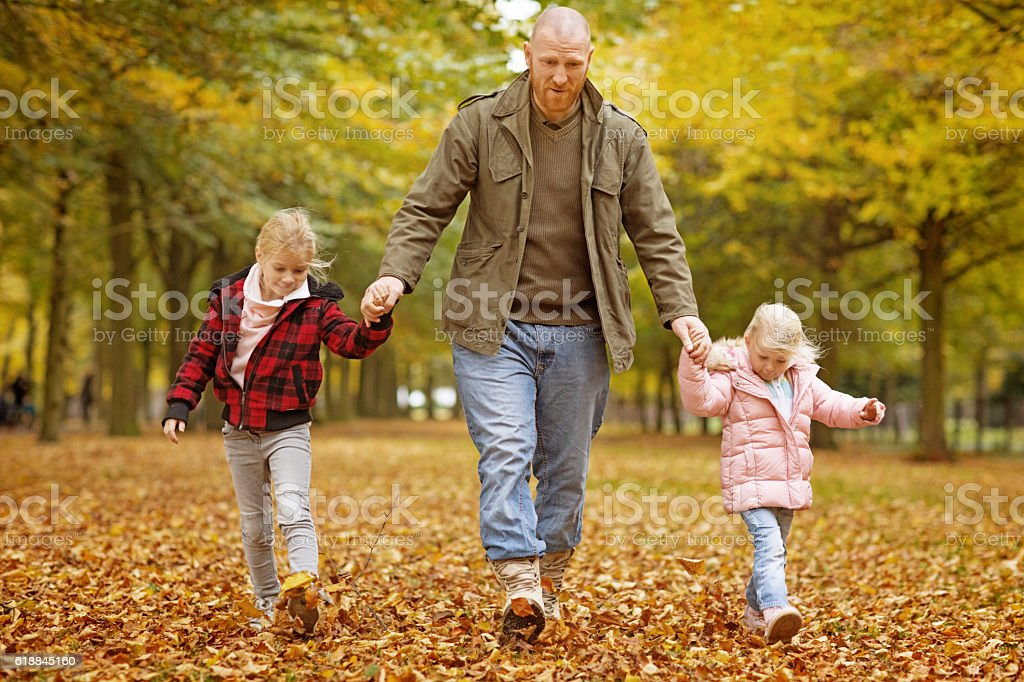 Single father and daughters walking together in autumnal park...