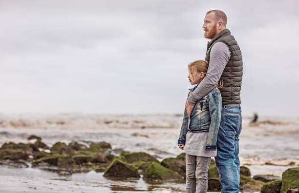 Single father and his daughter playing family games on a winter beach Handsome redhead single father and his blonde daughter playing family games on a winter beach mourner stock pictures, royalty-free photos & images