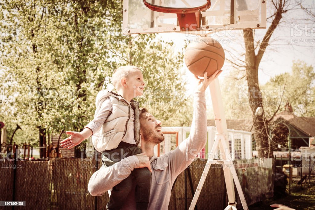 Father and his son playing basketball together.