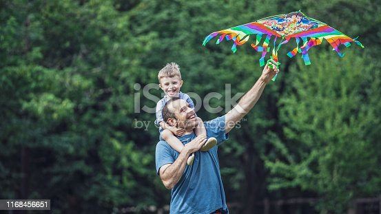 Single parent (father) spending quality time with his son in nature. Models on photo are real family. Picture taken in a park.