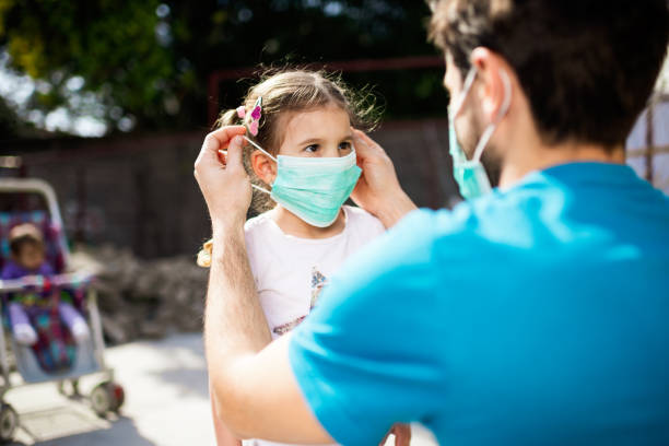 Single father applying pollution mask to his daughter Single father applying pollution mask to his daughter. They are outside. covid mask stock pictures, royalty-free photos & images