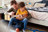 istock Single Father At Home With Son Teaching Him To Play Acoustic Guitar In Bedroom 1154943380