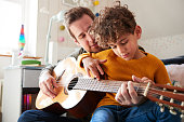 istock Single Father At Home With Son Teaching Him To Play Acoustic Guitar In Bedroom 1154945498